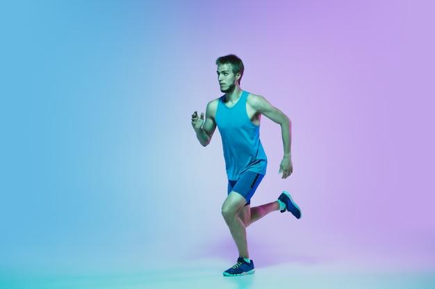 アクティブな若い白人ランニング、ネオンの光のグラデーションスタジオでジョギングの男性の完全な長さの肖像画