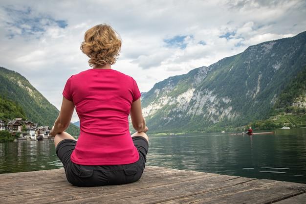 若い女性は、忙しいハイキングの後、山の湖の景色でリラックスします。