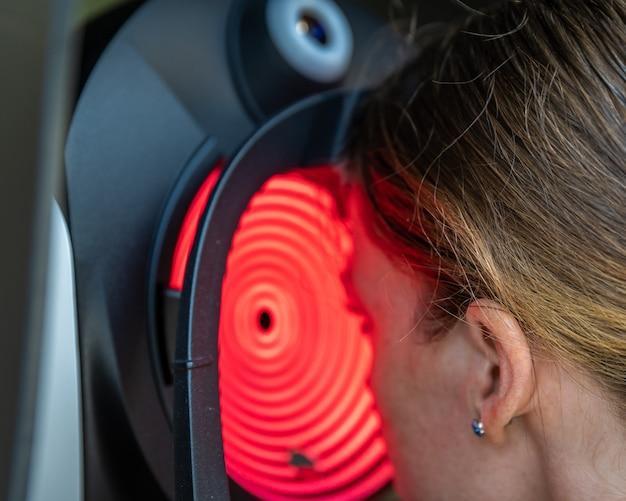 Визуальный осмотр глаз молодой женщины в глазной клинике