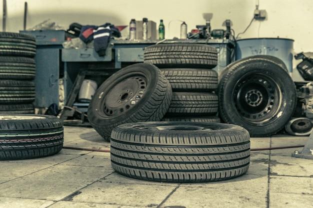 プロの工具の助けを借りて、プロのガレージで冬用タイヤを夏用タイヤに交換します。油圧ジャッキ上の車