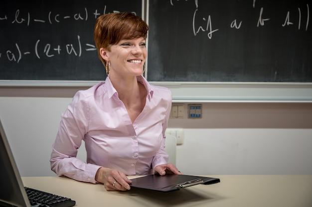 数学の学校で若い教師が講義し、黒板にチョークを書く