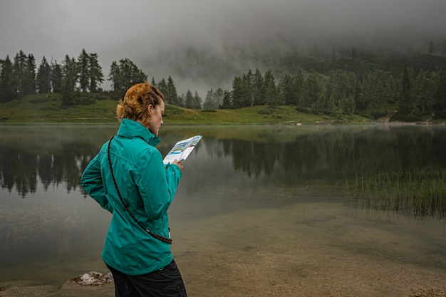 オーストリアアルプスのハイカーは、湖の周りの森の中の山道を歩く