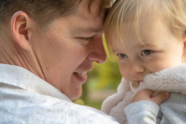 Счастливый папа с дочерью, наслаждаясь осенью в парке в прекрасную погоду