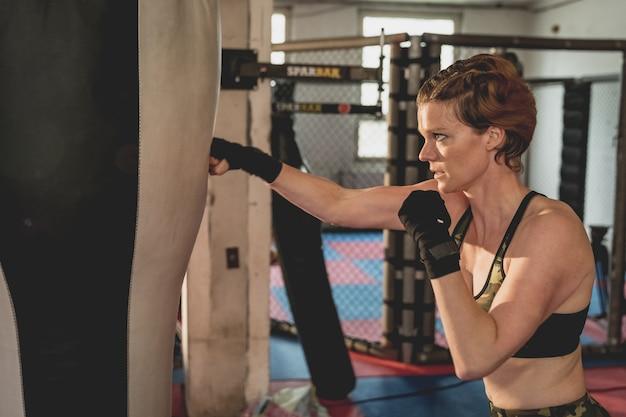 Шикарная женщина, боец мма в спортзале во время тренировки. подготовка к жесткой клетке
