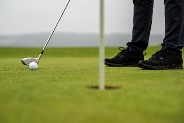 ゴルファーの精密ストライクがボールを穴に送り出す