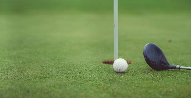 Игра в гольф на зеленом поле с мячом и клюшкой