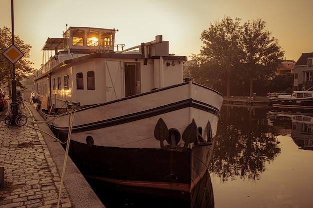 日の出のアムステルダムの運河に停泊するボート