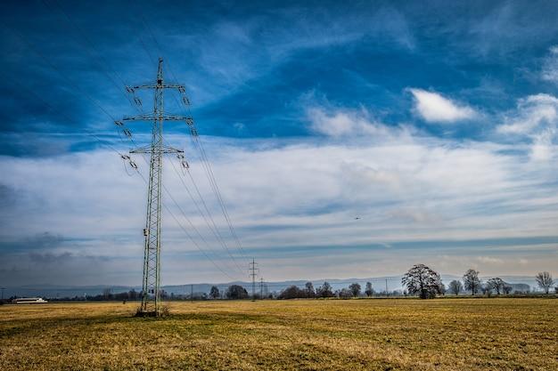 畑や牧草地を通る高圧送電線は、町や村に電力を供給します