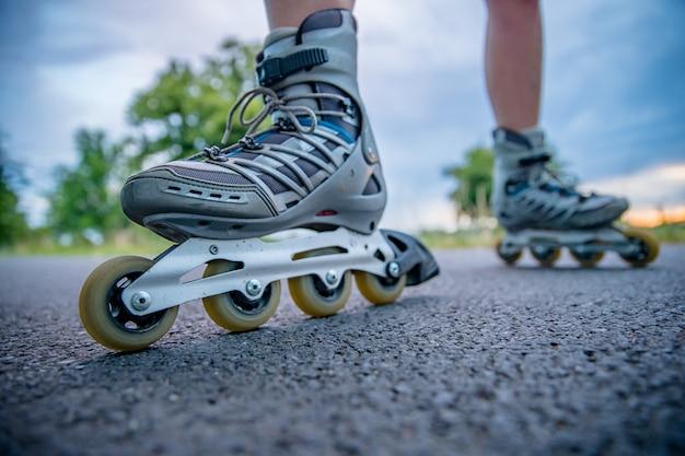 街の外のフリースタイルレースでアスファルトトレイルでアクションでローラースケート