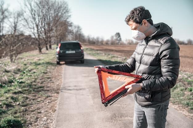 若い男は壊れた車の前の道路にオレンジ色の警告三角形をインストールします。人工呼吸器を使用したコロナウイルスからの保護