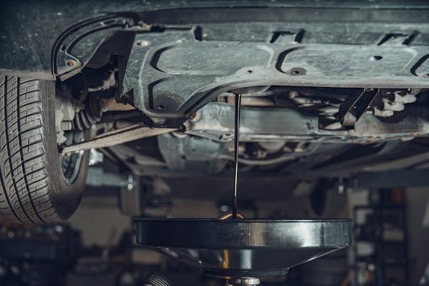 Слив отработанного масла из двигателя автомобиля в автосервисе