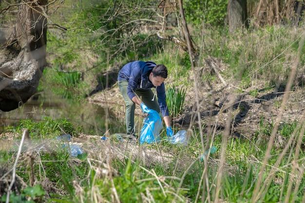 Собирая мусор в полиэтиленовый пакет, мужчина-волонтер помогает в лесу на берегу реки