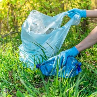 プラスチック廃棄物による地球の地球規模の汚染。ボランティアは、廃棄物を収集して森林や牧草地をきれいにすることで、生態学を助けます
