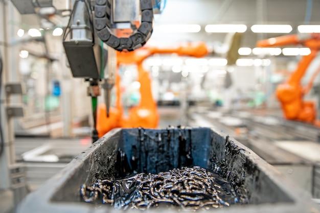 生産ラインでプラスチック部品を接着するロボットアーム用の黒い接着剤