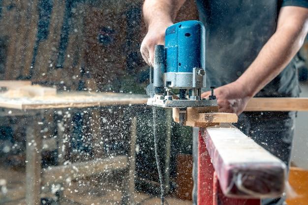 手動機械式カッターを使用して建具で木材を製粉します。おがくずが空を飛んでいます。コピースペース