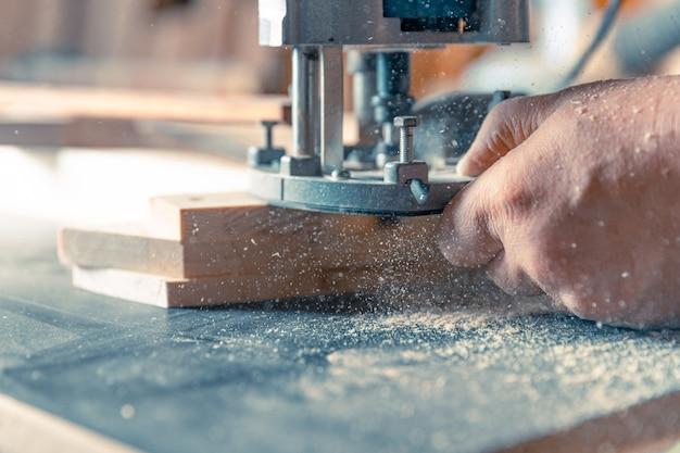 手動機械式カッターを使用して建具で木材を製粉します。おがくずを宙に舞う