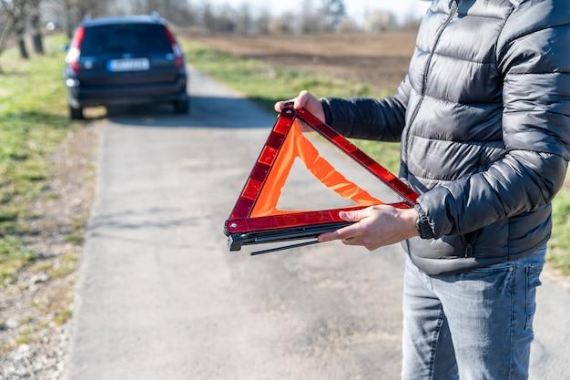 若い男は壊れた車の前の道路にオレンジ色の警告三角形をインストールします。