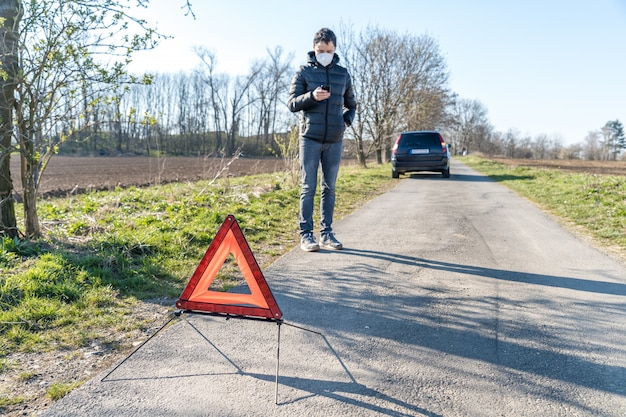 壊れた車の前の道路にある赤い警告トライアングル。電話を使用して支援サービスを注文する若い男性