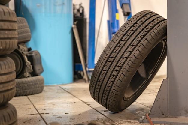 Ремонт и проверка автомобиля в ремонтной мастерской. опытный техник ремонтирует неисправную часть автомобиля. я меняю шины