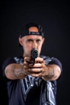 Человек, указывая пистолетом на объект, портрет на черном фоне