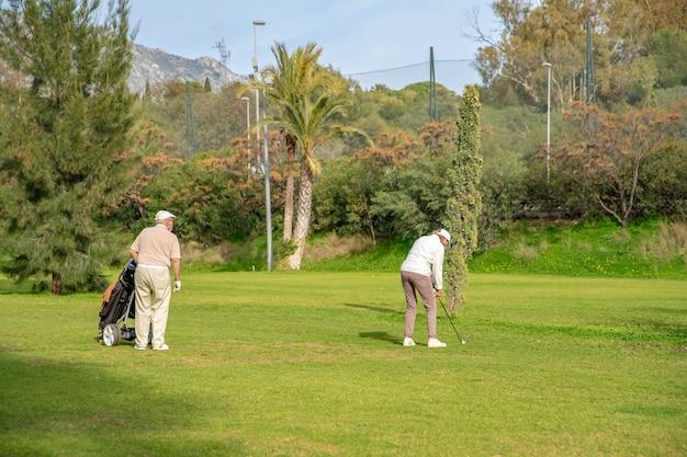 グリーンでゴルフをする年配のカップル