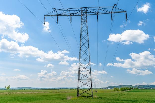農場の植物のフィールド上の高電圧ワイヤー