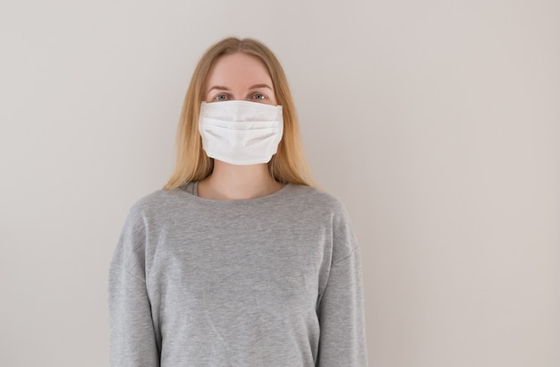 Портрет блондинке с зелеными глазами и длинными волосами в медицинской маске. понятие об эпидемии коронавируса и анти-смога.