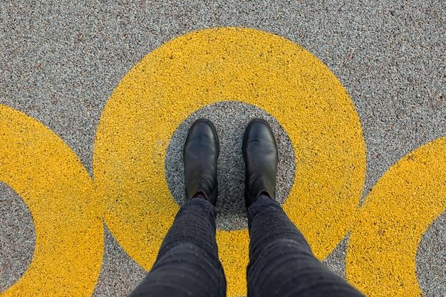 アスファルトのコンクリートの床に黄色の円で立っている黒い靴。コンフォートゾーンまたはフレームのコンセプト。快適ゾーンの円の中に立っている足