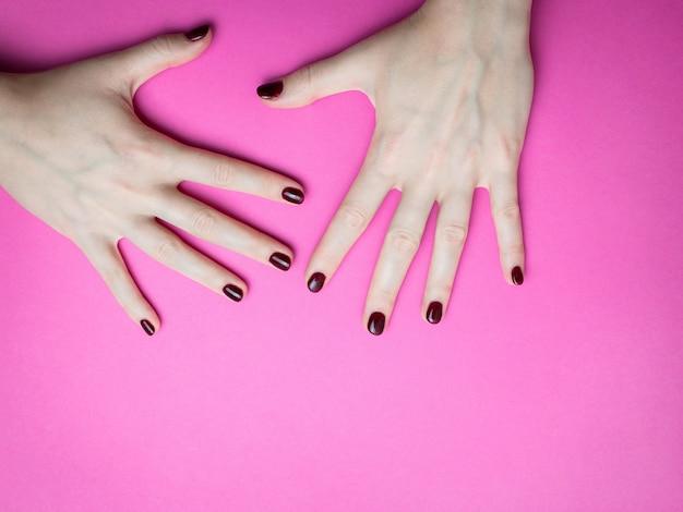 Стильный модный женский маникюр. руки красивой молодой женщины на розовом и голубом.