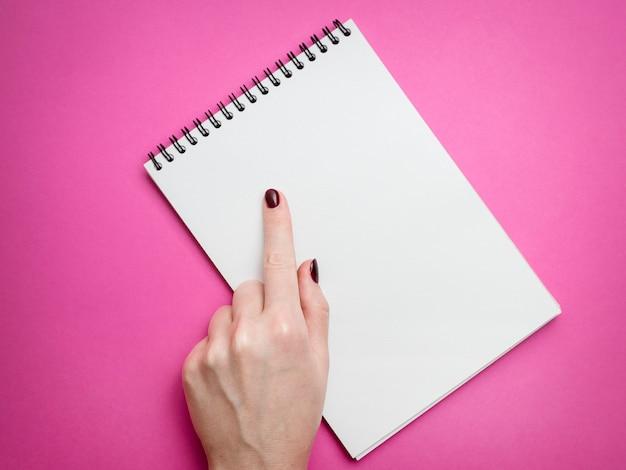 ハードカバーグレーリネンノートと白で隔離されるボールペンを持っている人間の手の平面図