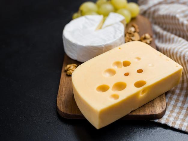 木製のまな板の上のチーズ、ナッツ、ブドウのバリエーション。カマンベールチーズとエダムチーズ。ワインとロマンチックな料理