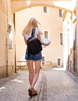 ヨーロッパの歴史的な街のアーケードを歩く女性旅行者。ヨーロッパの地図と一緒に旅行する内気な少女。