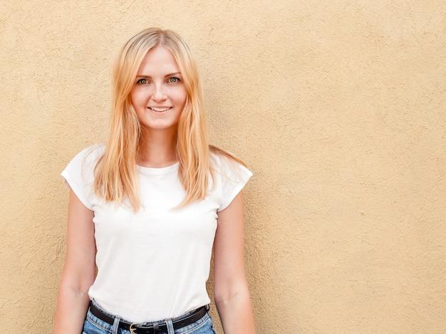 Девушка битника нося пустую белую футболку и джинсы представляя против грубой уличной стены, минималистского городского стиля одежды