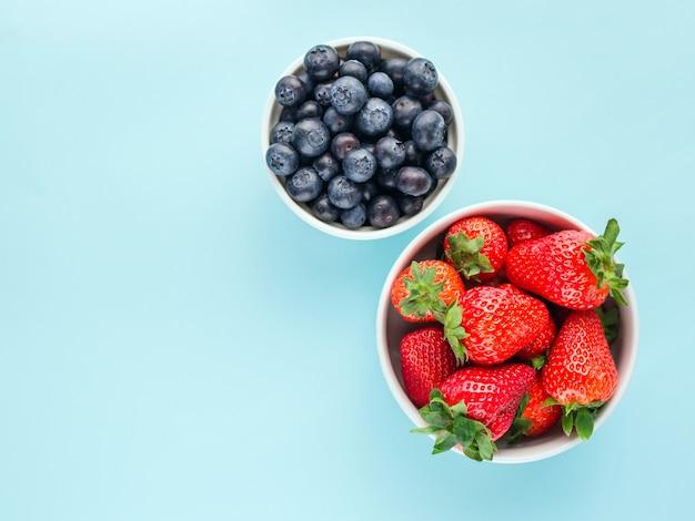 イチゴとブルーの明るい背景に白いボウルのブルーベリー