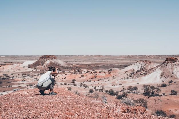 女性写真家と旅行者は、壮観な砂漠の人里離れた場所で写真を撮っています