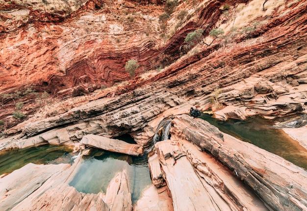 カリジニ、ハマースリー渓谷の斜めと曲線の形を撮影する男性カメラマン。