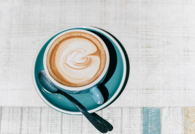 Стильная чашка кофе с латте-арт на белом фоне таблицы
