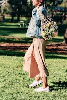 メッシュの再利用可能なコットンバッグで食料品を買う女性。