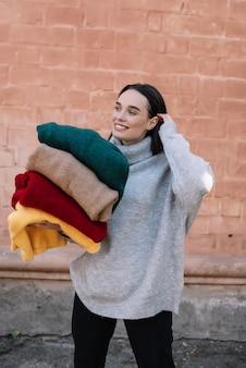 Счастливая молодая девушка в вязаном сером свитере улыбается и смотрит в сторону, держа красочные одеяла