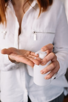 抗菌石鹸消毒剤を噴霧する女性。閉じる