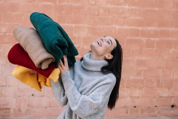 Молодая девушка в вязаном сером свитере улыбается и наслаждается красочными одеялами