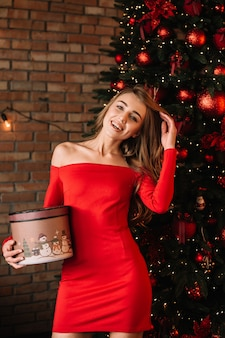 Красивая девушка в сексуальном красном платье с подарочной коробкой возле елки