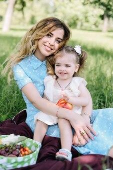 若い母親が公園で彼女の小さな娘と遊ぶ、彼女の手につかまって