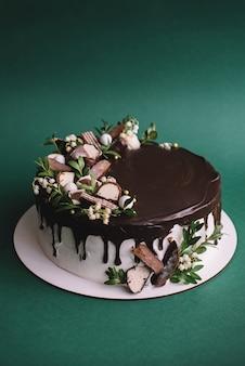 チョコレートチップクッキー、緑の背景にお菓子で飾られたチョコレートケーキ。