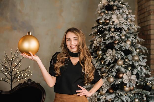 Счастливая девушка с мячом в руке. рождественские украшения