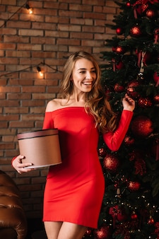 クリスマスツリーの近くのエレガントなラッドドレスの若い女性