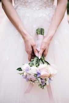 Невеста в белом платье держит букет с цветами роз. свадебный день и церемония