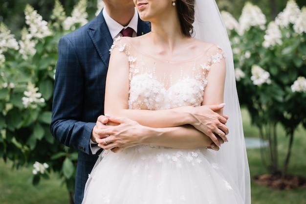 Жених держит невесту в объятиях в саду