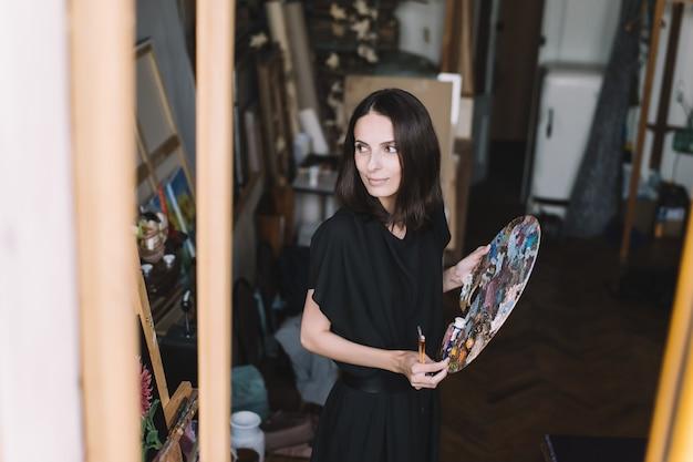 アートスタジオで絵を描いている女性アーティスト。女性アーティスト、描画プロセス。