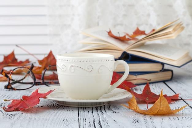 一杯のコーヒー、開いた本、木製の表面の葉とアップリケ